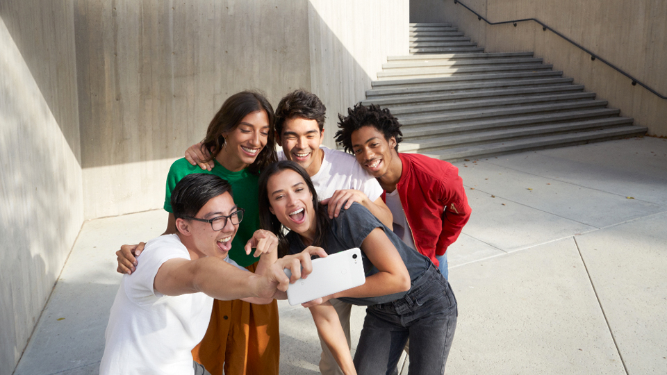 Young people taking a group selfie with the Google Pixel 3